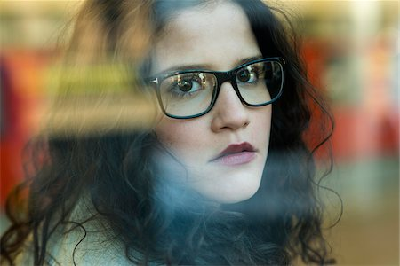 Close-up portrait of teenage girl wearing eyeglasses and looking out window, Germany Stock Photo - Rights-Managed, Code: 700-07310977