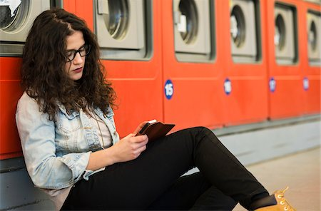 Teenage girl sitting on floor next to dryers, in laundromat, Germany Stock Photo - Rights-Managed, Code: 700-07310978