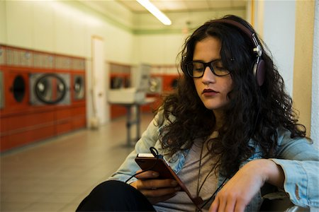 Teenage girl sitting in laundromat, wearing headphones and listening to music on smart phone, Germany Stock Photo - Rights-Managed, Code: 700-07310981