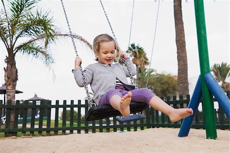 Three year old girl playing in playground on swing, Spain Stock Photo - Rights-Managed, Code: 700-07311135