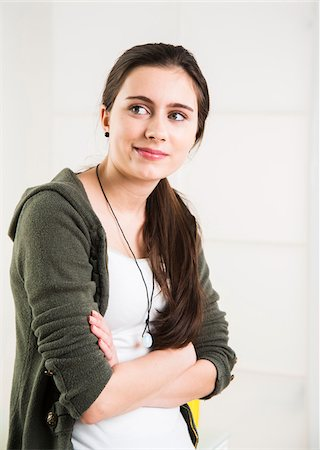 pretty - Portrait of teenage girl with arms crossed, looking to the side and smiling, studio shot on white background Stock Photo - Rights-Managed, Code: 700-07311428