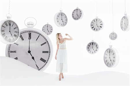 Young woman wearing white dress, standing in abstract landscape with pocket watches hanging in sky, studio shot Stock Photo - Rights-Managed, Code: 700-07487679