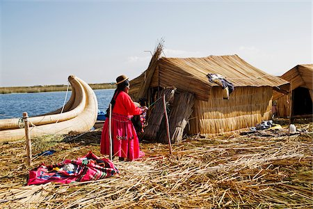 peru and culture - Woman in Peruvian clothing standing next to straw house, Floating Island of Uros, Lake Titicaca, Peru Stock Photo - Rights-Managed, Code: 700-07529097