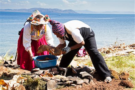 peru and culture - Man and woman in Peruvian clothing tending to earth covered barbeque, Taquile Island, Lake Titicaca, Peru Stock Photo - Rights-Managed, Code: 700-07529101