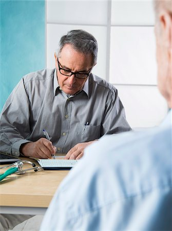 Senior, male doctor conferring with male patient in office, Germany Stock Photo - Rights-Managed, Code: 700-07529239