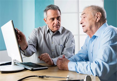 Senior, male doctor conferring with senior, male patient, using desktop computer in office, Germany Stock Photo - Rights-Managed, Code: 700-07529232