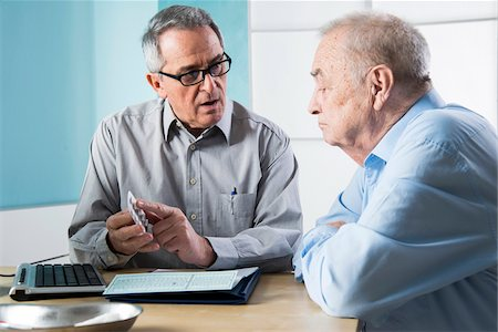 Senior, male doctor conferring with senior, male patient in office, discussing medication, Germany Stock Photo - Rights-Managed, Code: 700-07529233