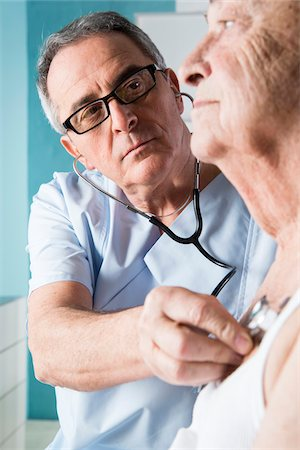 Senior, male doctor using stethoscope on senior, male patient, in office, Germany Stock Photo - Rights-Managed, Code: 700-07529244