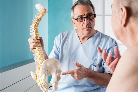 Senior, male doctor discussin spinal cord with senior, male patient, in office, Germany Stock Photo - Rights-Managed, Code: 700-07529248