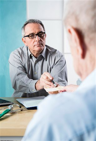 Senior, male doctor conferring with male patient in office, Germany Stock Photo - Rights-Managed, Code: 700-07529241