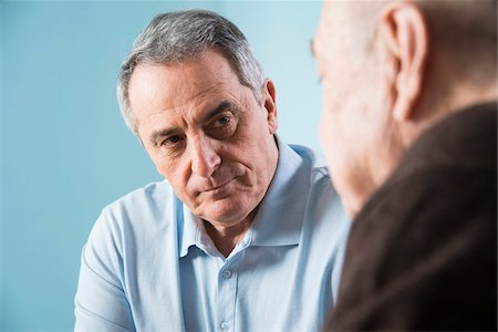 Close-up of senior, male doctor conferring with senior, male patient in office, Germany Stock Photo - Rights-Managed, Code: 700-07529268