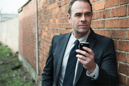 front - Portrait of businessman standing next to brick wall outdoors, holding cell phone, Germany Stock Photo - Rights-Managed, Code: 700-07529283