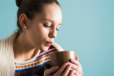 Close-up of teenage girl holding mug and blowing on hot drink, studio shot on blue background Stock Photo - Rights-Managed, Code: 700-07567439