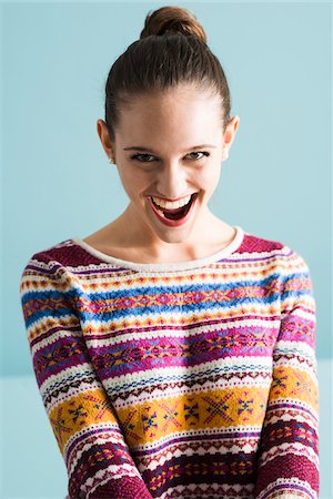 Close-up portrait of teenage girl with hair in bun, looking at camera and smiling with open mouth, studio shot on blue background Stock Photo - Rights-Managed, Code: 700-07567444