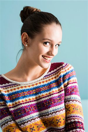 Close-up portrait of teenage girl with hair in bun, looking at camera and smiling, studio shot on blue background Stock Photo - Rights-Managed, Code: 700-07567445