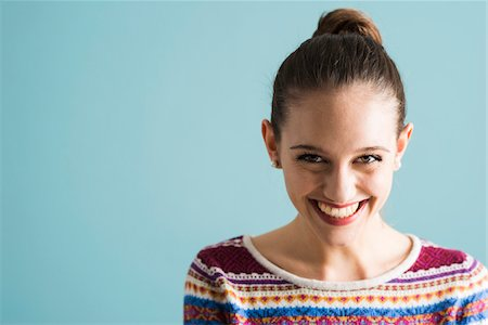Close-up portrait of teenage girl with hair in bun, looking at camera and smiling, studio shot on blue background Stock Photo - Rights-Managed, Code: 700-07567447