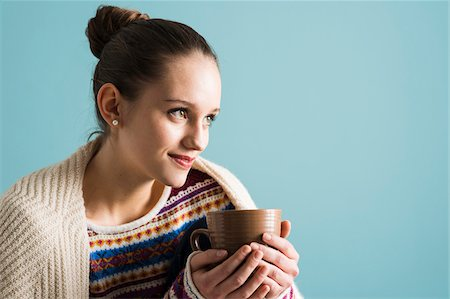 Close-up portrait of teenage girl with hair in bun, holding mug and looking into the distance, studio shot on blue background Stock Photo - Rights-Managed, Code: 700-07567440