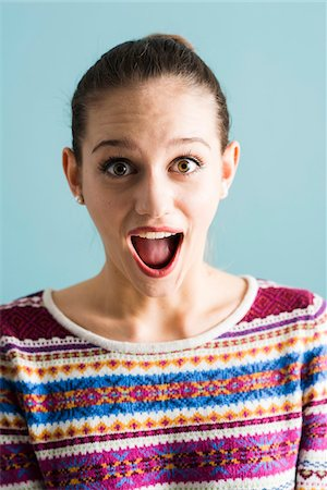 expresivo - Close-up portrait of teenage girl, wide-eyed and with open mouth, studio shot on blue background Foto de stock - Con derechos protegidos, Código: 700-07567451