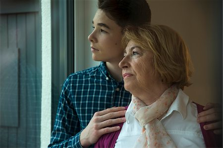 Close-up portrait of teenage boy with grandmother looking out window at home, Germany Stock Photo - Rights-Managed, Code: 700-07584804