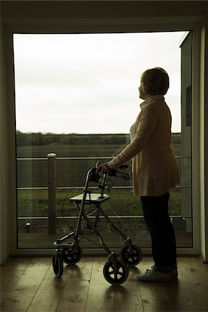 Senior woman using walker, standing and looking out of window, Germany Stock Photo - Rights-Managed, Code: 700-07584815
