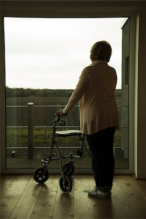 Senior woman using walker, standing and looking out of window, Germany Stock Photo - Rights-Managed, Code: 700-07584816