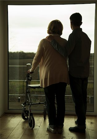 Grandmother using walker standing beside teenage grandson, and looking out of window, Germany Stock Photo - Rights-Managed, Code: 700-07584817