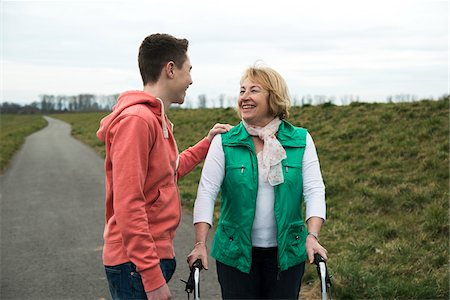 Teenage grandson talking to grandmother using walker on pathway in park, walking in nature, Germany Stock Photo - Rights-Managed, Code: 700-07584819