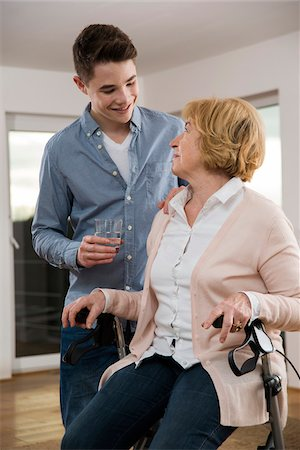 Teenage boy helping Grandmother sitting in walker at home, getting glass of water, Germany Stock Photo - Rights-Managed, Code: 700-07584811