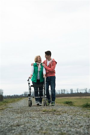 Teenage grandson with grandmother using walker on pathway in park, walking in nature, Germany Stock Photo - Rights-Managed, Code: 700-07584826