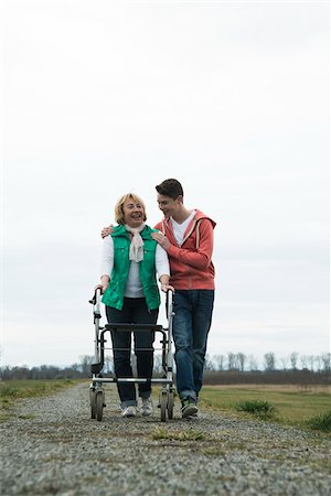 Teenage grandson with grandmother using walker on pathway in park, walking in nature, Germany Stock Photo - Rights-Managed, Code: 700-07584827