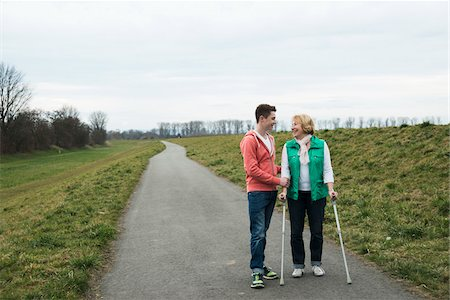 Teenage grandson talking to grandmother using crutches on pathway in park, walking in nature, Germany Stock Photo - Rights-Managed, Code: 700-07584831