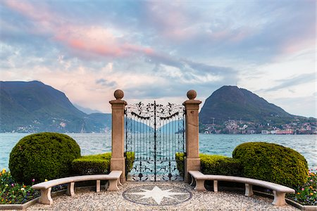 Ornamental topiary, globe shaped bushes next to wrought iron gate in Parco Civico in front of Monte San Salvatore in spring at sunset, Lugano, Switzerland Stock Photo - Rights-Managed, Code: 700-07672084