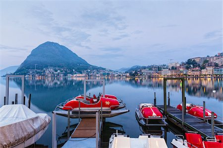 Moored pedal boats by the promenade in front of Monte San Salvatore and city lights at Lago Lugano at dawn in spring, Lugano, Switzerland Stock Photo - Rights-Managed, Code: 700-07672086