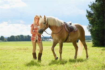 equestrian - Portrait of a young woman standing beside her Haflinger horse in a field in summer, Upper Palatinate, Bavaria, Germany Stock Photo - Rights-Managed, Code: 700-07734359
