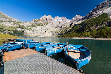 Blue rowing boats in front of the steep mountains of the Bluemlisalp Mountain Range at Lake Oeschinensee, Kandersteg, Jungfrau-Aletsch, UNESCO World Heritage Site, Canotn of Bern, Switzerland Stock Photo - Rights-Managed, Code: 700-07844388