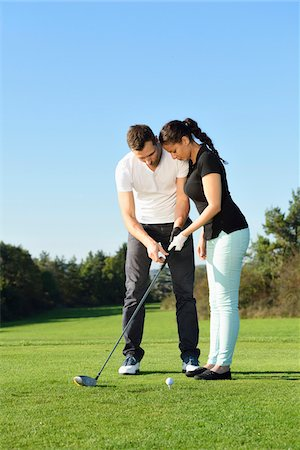 Man Showing Woman how to Play Golf on Golf Course in Autumn, Bavaria, Germany Stock Photo - Rights-Managed, Code: 700-07942513