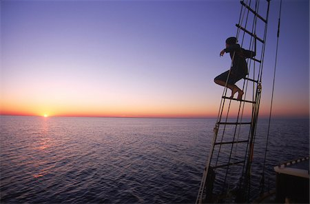 Man Watching Sunset from Rigging aboard Tree of Life Stock Photo - Rights-Managed, Code: 700-07965864