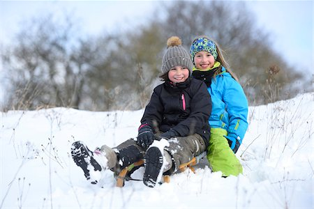 sole - Portrait of two girls playing in the snow with sled, winter, Bavaria, Germany Stock Photo - Rights-Managed, Code: 700-07991773