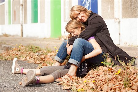 Portrait of mother and daughter sitting on curb on sidewalk in autumn, painted doors of abandoned stables in background, Vendome, Loir-et-Cher, France Stock Photo - Rights-Managed, Code: 700-08059741