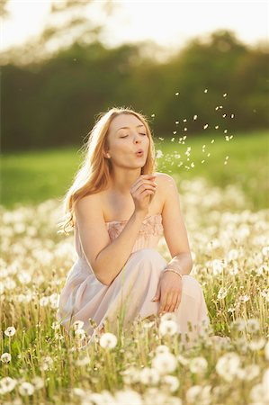Young woman sitting in a withered dandelion meadow in spring, Germany Stock Photo - Rights-Managed, Code: 700-08080547