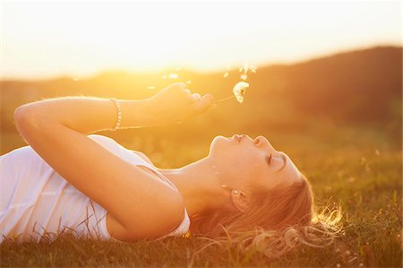 Young woman holding a dandelion in her hand lying on a meadow at sunset in spring, Germany Stock Photo - Rights-Managed, Code: 700-08080556