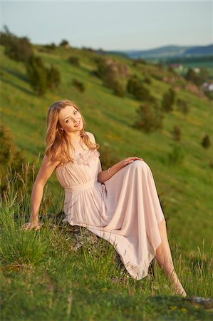 pink - Young woman sitting in a meadow at sunset in spring, Germany Stock Photo - Rights-Managed, Code: 700-08080550