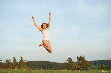 Young woman jumping in the air on a meadow in spring, Germany Stock Photo - Rights-Managed, Code: 700-08080551