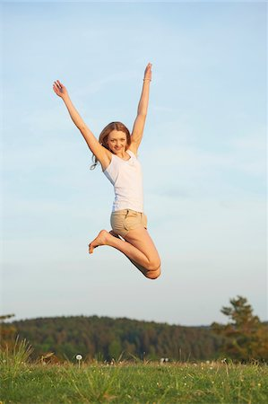 Young woman jumping in the air on a meadow in spring, Germany Stock Photo - Rights-Managed, Code: 700-08080552