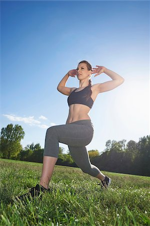 female only - Close-up of a young woman exercising, stretching in a park in spring, Bavaria, Germany Stock Photo - Rights-Managed, Code: 700-08080564