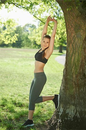 female only - Close-up of a young woman exercising, stretching beside a tree in a park in spring, Bavaria, Germany Stock Photo - Rights-Managed, Code: 700-08080568