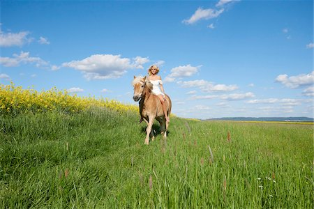 Young woman riding a Haflinger horse in a meadow in spring, Bavaria, Germany Stock Photo - Rights-Managed, Code: 700-08080584