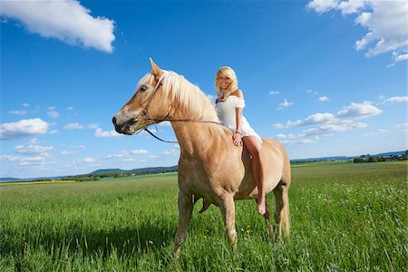 sexy women legs - Portrait of a young woman sitting on a Haflinger horse in a meadow in spring, Bavaria, Germany Stock Photo - Rights-Managed, Code: 700-08080582