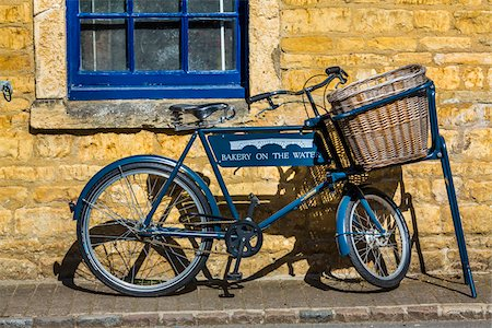 Close-up of bicycle with wicker basket basket parked on sidewalk, Bourton-on-the-Water, Gloucestershire, The Cotswolds, England, United Kingdom Stock Photo - Rights-Managed, Code: 700-08122111