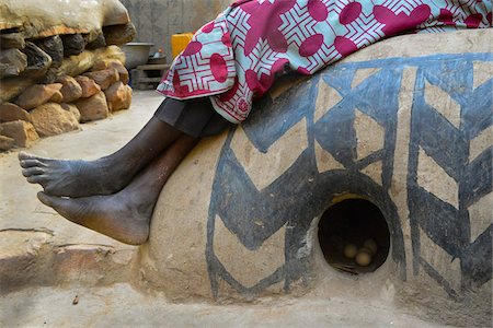 Close-up of woman's legs and feet, sitting on decorated round henhouse with eggs, Tiebele, Burkina Faso Stock Photo - Rights-Managed, Code: 700-08171609